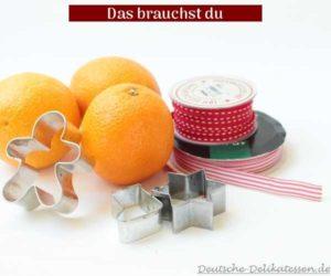 Apfelsinen mit Keksausstecher und Geschenkband