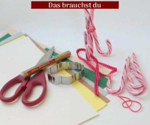 Zuckerstangen, Gummiband, Geschenkband, Bastelkarton Stift und Schere als Bastelmaterial für das Platzkärtchen.