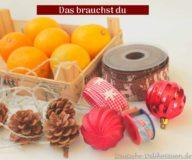 Eine Kiste mit Mandarinen, Lichterkette, Zapfen, rote Weihnachtskugeln, Geschenkband, Klebeband.