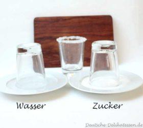 Gläser auf Tellern mit Zucker und Wasser