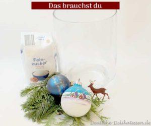 Glas, Zucker, Weihnachtskugeln, Hirsch und Tannenzweige.