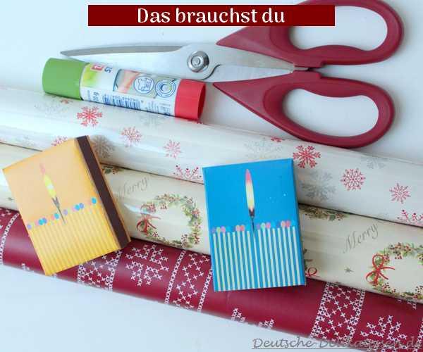 Weihnachtsgeschankpapier, Streichholzschachteln, Schere und Klebestift.