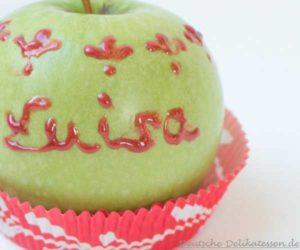 Grüner Apfel mit roter Schrift als Namenskarte auf dem Tisch.