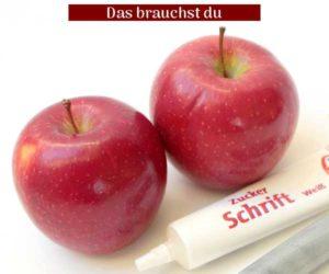 Rote Äpfel und weisse oder silberfarbene Zuckerschrift als Material.