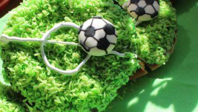 Amerikaner Gebäck dekoriert mit grünen Kokosstreusseln und Fussball Aufleger