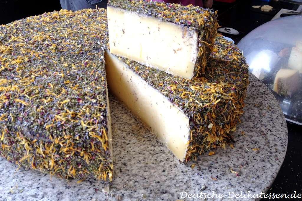 Großer runder Käse aufgeschnitten mit Heublüten