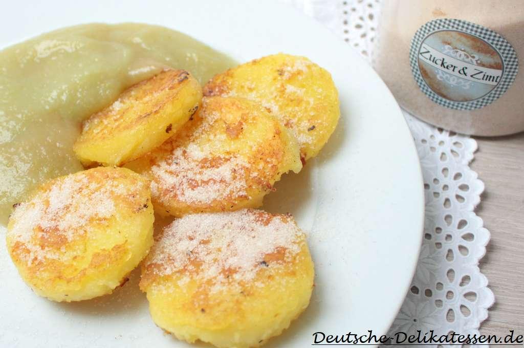 Gebratene Kloßscheiben mit Zucker Zimt und Apfelmus auf einem weißen Teller