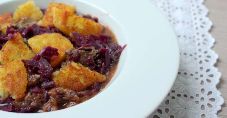 Gebratene Klösse mit Bratenfleisch, Rotkraut und Sosse in einem Teller