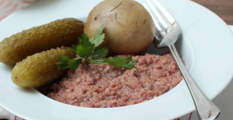 Teller mit warmen Weckewerk und Pellkartoffeln und sauren Gurken