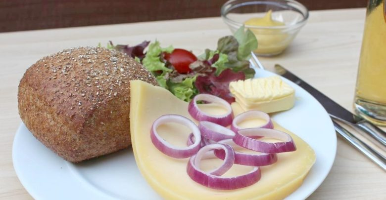Halver Hanh: Röggelchen mit Käse, Zwiebel, Butter und Senf auf einem Teller