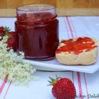 Sebst gemachte Erdbeermarmelade im Glas mit Marmeladenbrötchen und einer Holunderdolde