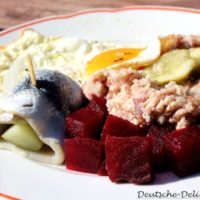 Labskaus mit Rollmops, Spiefelei und Rote Beete auf einem Teller.